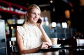 stock photo of mobile-phone  - A young woman having coffee in a cafe and talking on her cell phone - JPG