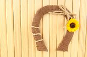Decorative horseshoe of straw with sunflower, on wooden background