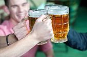 stock photo of stein  - Friends with a fresh beer in a Beer pub. close-up on beer stein