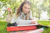 Pretty smiling student lying on the grass studying with her tablet pc on college campus