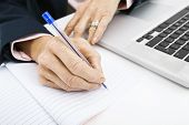 Cropped image of businesswoman with laptop writing in book on office desk