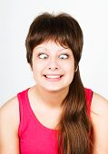 stock photo of wacky  - cross eyed squinting expression young girl - JPG