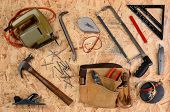 Overhead view of construction equipment and tools laid out on a sheet of plywood. Items include, ham