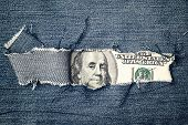 Hundred Dollars Bill Through Torn Blue Jeans Texture