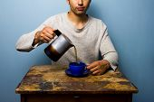 Young Man At Wooden Table Pouring Coffee
