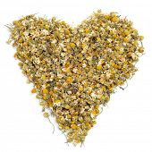 a pile of dried chamomile flowers forming a heart on a white background