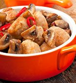 stock photo of sauteed  - Sauteed chicken with mushrooms on orange pan - JPG