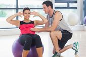 Male trainer helping young woman do abdominal crunches on fitness ball at a bright gym