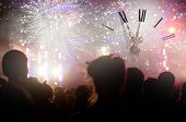 Clock close to midnight, fireworks and crowd waiting for New year