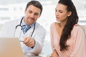 Male doctor showing something on laptop to patient in medical office
