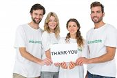 Group portrait of happy volunteers holding 'thank you' board over white background