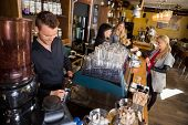 Male bartender working at counter while female colleague serving coffee to customer