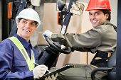 Portrait of young forklift driver with supervisor writing notes at warehouse