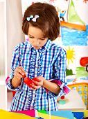 Child making decoration card with bow.