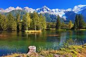 stock photo of snow capped mountains  - Lake with cold water surrounded by trees and snow - JPG