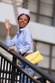 picture of jamaican  - Stock image of a young Jamaican woman smiling and waving her hand - JPG