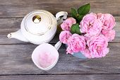 Breakfast tea with  teapot of fresh pink garden roses on color wooden background