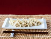 Gyoza Or Potstickers On Bamboo Mat With Copy Space