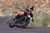 stock photo of crotch-rocket  - Speeding motorcycle racing around a corner on a country back road - JPG