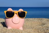 foto of piggy  - Summer piggy bank with sunglasses on the beach - JPG