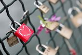 Closeup on a red padlock with a studded heart on a bridge railing. Selective focus on the red padlock.