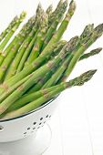 green asparagus in colander on white background