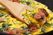 Frittata With Tomato, Ham And Herbs On Wooden Spatula.