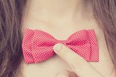 Stylish Young Girl Holding A Bow-tie Near The Neck