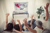 stock photo of indoor games  - Family cheering and watching the world cup at home in the living room - JPG