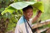 BAAN LOOK KAO LAM, THAILAND, NOVEMBER 19 : portrait of a Lahu tribe man using a banana tree leaf as