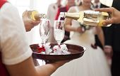 Waiter serving champagne to bride and groom