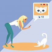 Blond woman is taking a snapshot of the cat for social networking
