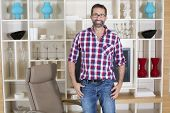 picture of united we stand  - handsome man standing in living room in front of a wall unit - JPG