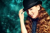 Portrait of an elegant teen girl wearing retro dress and bowler hat.
