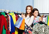 Two happy female friends with clothes in shop