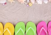 Bright flip-flops on sand, close up