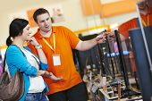 pic of supermarket  - Young woman choosing tv set with shop assistant in home appliance shopping mall supermarket - JPG