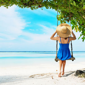 stock photo of swing  - Woman in blue dress swinging at tropical beach - JPG