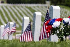 stock photo of veterans  - veterans cemetery memorial celebration with American Flag - JPG