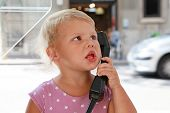 Caucasian Blond Girl Talking On The Street Phone