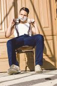 Handsome Man With Shaving Foam On His Face And Towel Around His Neck Siting On Chair And  Posing In