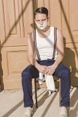 Handsome Man With Shaving Foam On His Face And Towel Around His Neck Siting On Chair And  Posing