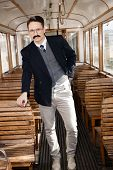 Man With A Mustache In A Suit With Glasses Posing In An Old Train Wagon Or Carriage