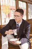 Photo Of Man With Mustache And Glasses On Train Wooden Wagon Drinking Coffee Or Tea From Cup And Loo