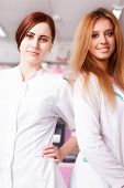 Two Nurses In Pharmacy Smiling At Camera
