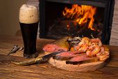 Glass Of Dark Beer And A Fish Platter On The Background Of A Burning Fireplace