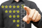 stock photo of benchmarking  - business man pressing five star rating isolated - JPG