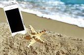 Starfish And Mobile Phone On The Beach
