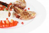 meat portion: barbecued ribs served with rice and tomatoes on plate over white background