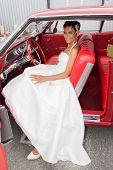 Happy Caucasian Bride in a red car